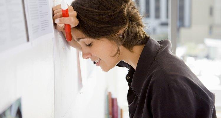 Mulher recostando a cabeça na parede do trabalho