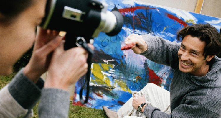 Woman filming man painting with digital video camera