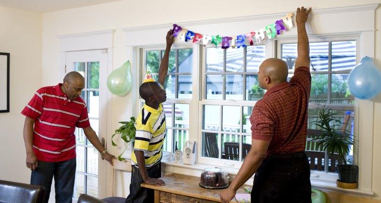 Men and boy hanging birthday decorations