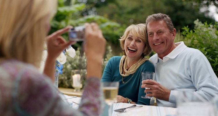 Woman taking photograph of couple at lunch table outdoors, smiling