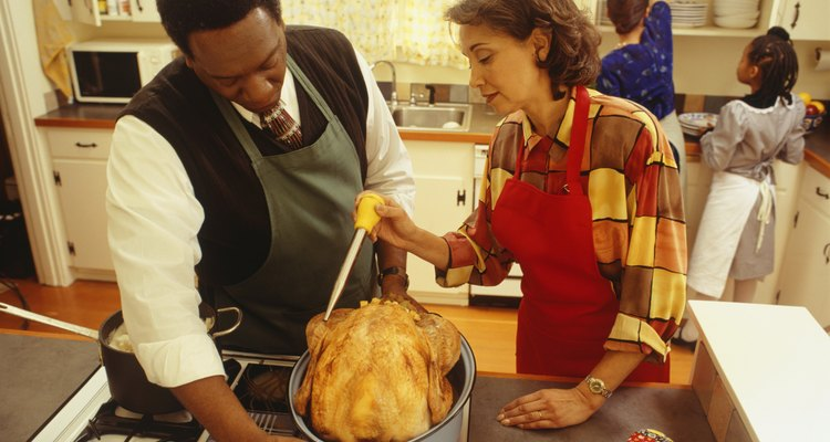 Couple basting thanksgiving turkey