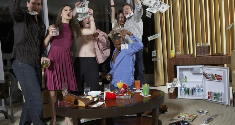 Group of people celebrating in hotel room, throwing  US dollar notes