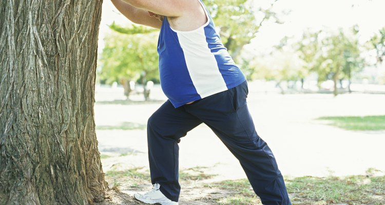 Overweight man in park,stretching against tree,side view
