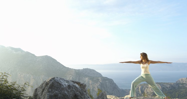 Young woman performing stretching exercises on rock near sea