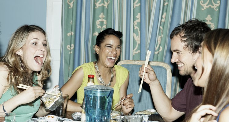 Grupo de amigas comendo com pauzinhos