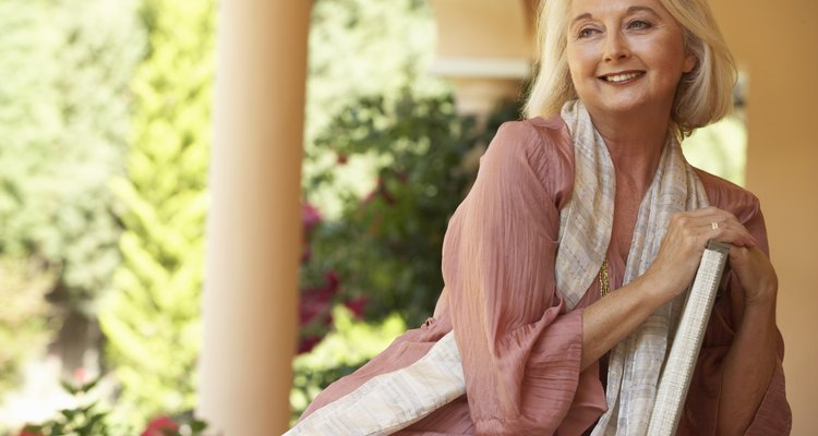 Senior woman sitting on chair on porch, smiling