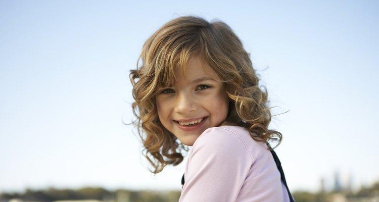 Girl (8-9) against clear sky, smiling, portrait