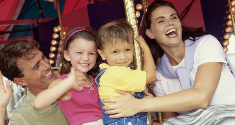 Young couple sitting on a carousel with their son and daughter