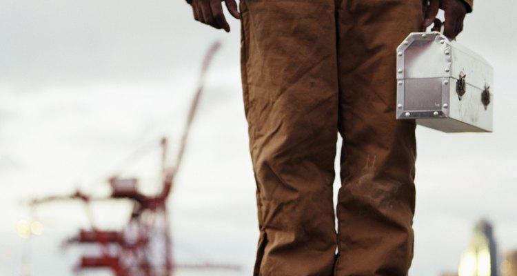 Trabalhador segurando marmita de metal