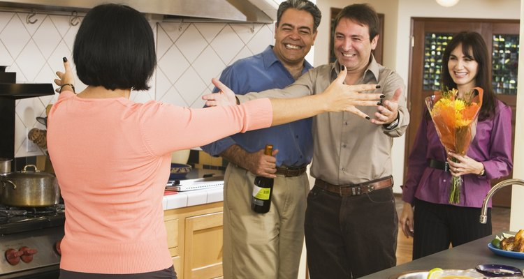 Middle-aged friends greeting in kitchen
