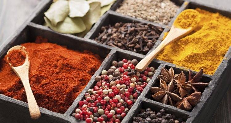 spices box: pink black pepper, paprika powder, curry, bay