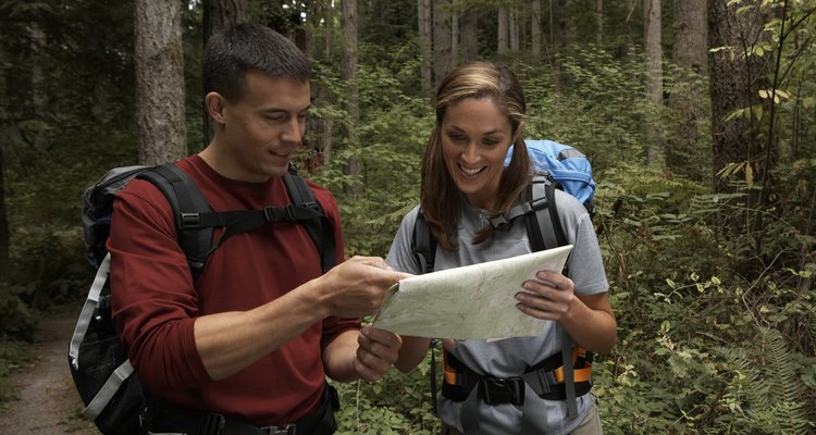 Man and woman looking at topographical map in forest, smiling