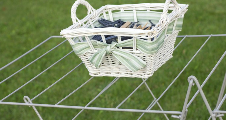 Wicker basket of clothes pegs on a wire drying stand.
