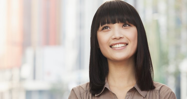 Portrait of smiling young woman outdoors in Beijing, looking up