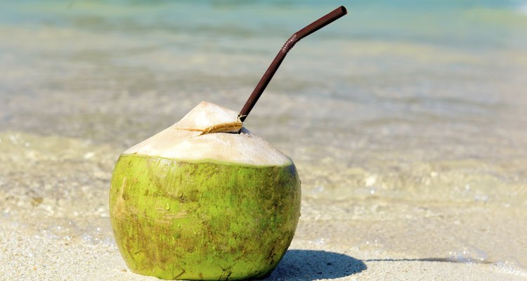 Opened coconut with a straw on summer beach.