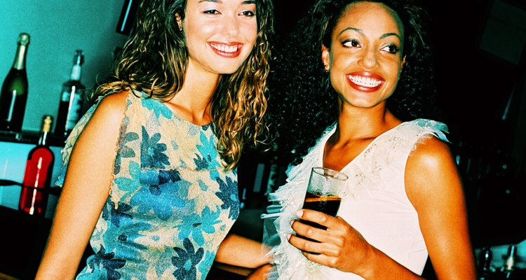 shot of two women standing at a bar counter with drinks
