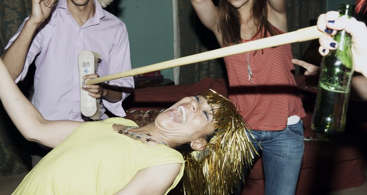 Friends playing game of limbo at house party