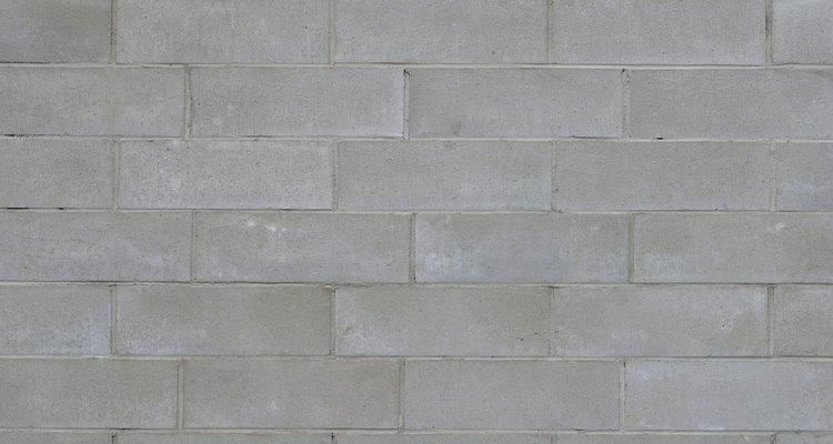 Cubre la superficie rugosa de tu pared de bloques de hormigón con placas de hormigón.