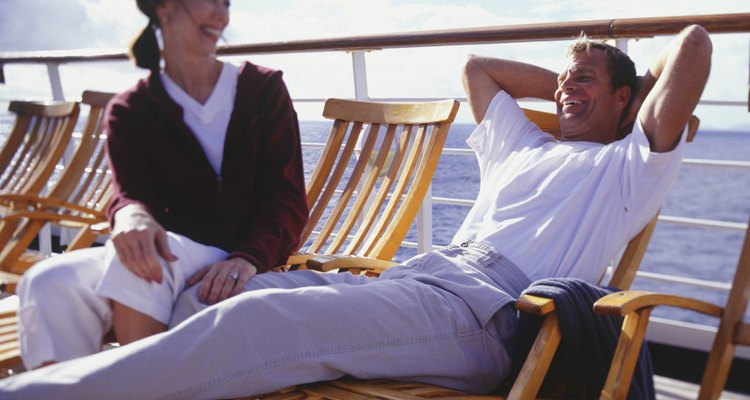 Couple sitting on deck chairs on cruise ship