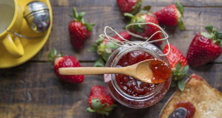 Strawberry jam, fresh strawberries on wooden background
