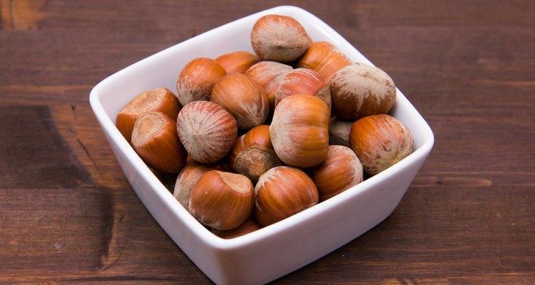 Hazelnuts on square bowl on wood