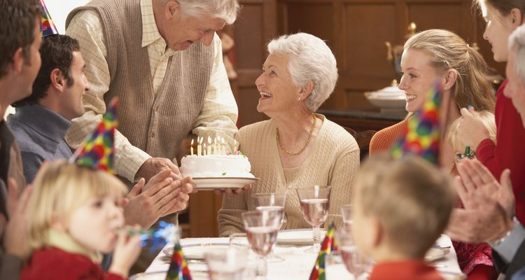Grandmother getting her birthday cake at the table with family