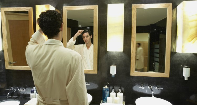 Man in robe in front of bathroom mirror
