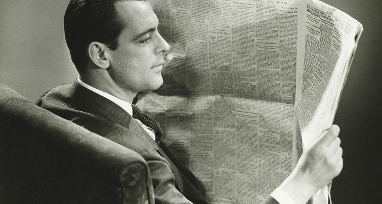 Businessman reading newspaper at home, (B&W)