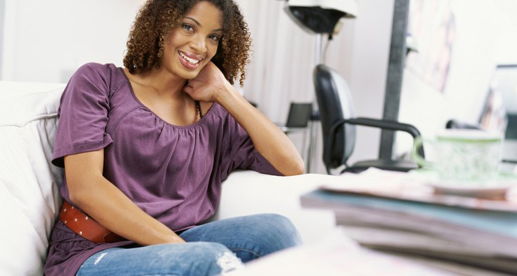 Low angle view of a young woman waiting in a beauty salon, smiling