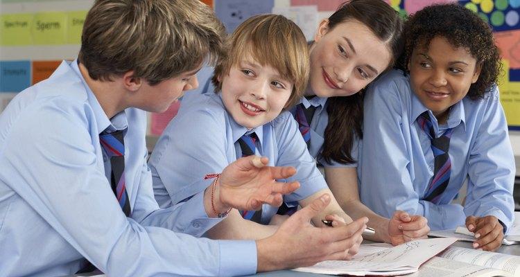 Estudiantes de preparatoria en uniforme trabajando juntos.