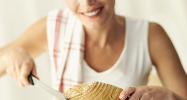 Young woman slicing a loaf of freshly baked bread