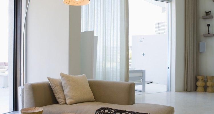 Las cortinas blancas que van desde el piso hasta el techo producen un efecto dramático en esta moderna habitación.