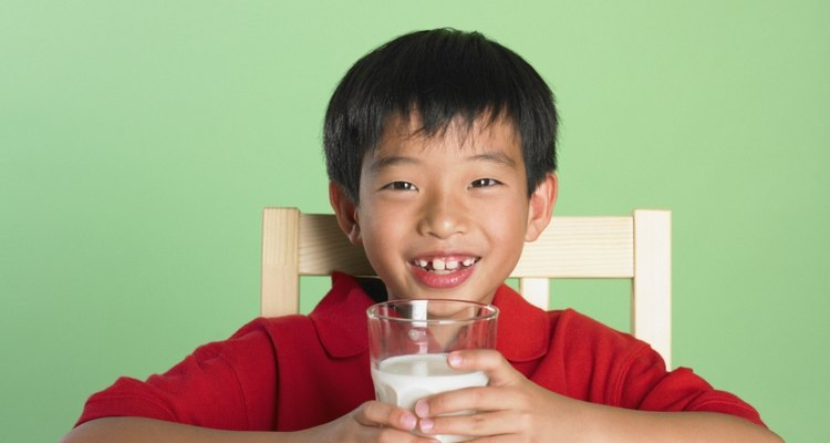 Portrait of Asian boy holding glass of milk