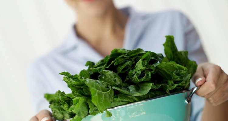 woman holding a colander of washed greens (selective focus)