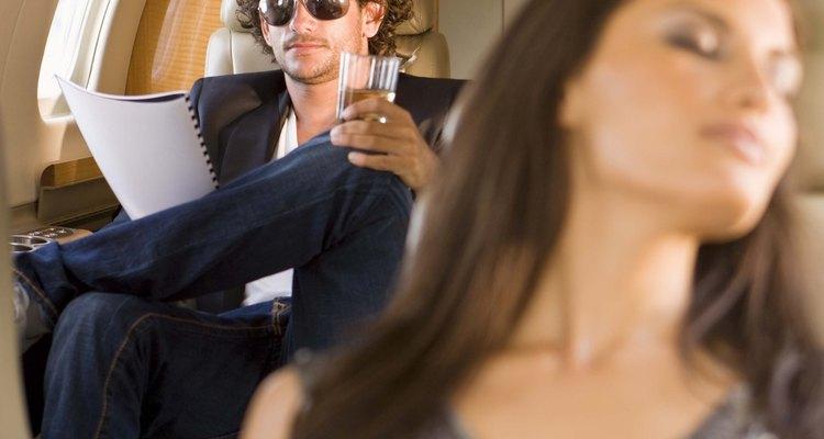 Algunos pasajeros duermen sentados en un avión.