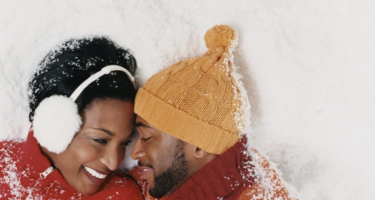 Couple Wearing Warm Clothing Lying in the Snow and Gazing at Each Other