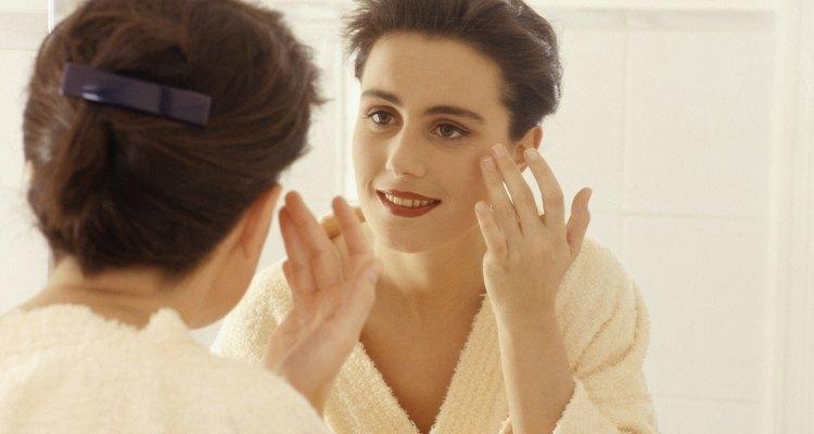Woman applying cosmetics in mirror
