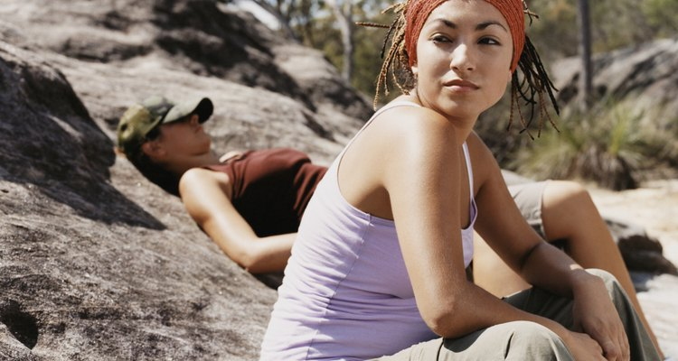 Young Woman Sitting on a Rock With Another Woman Lying in the Background