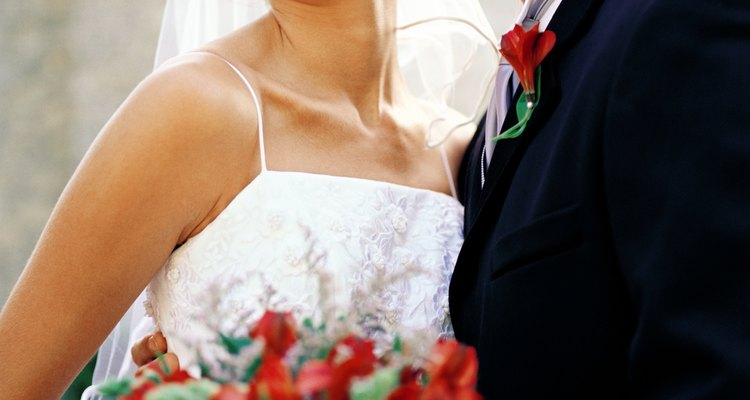 portrait of the bride and groom standing with a bouquet of flowers