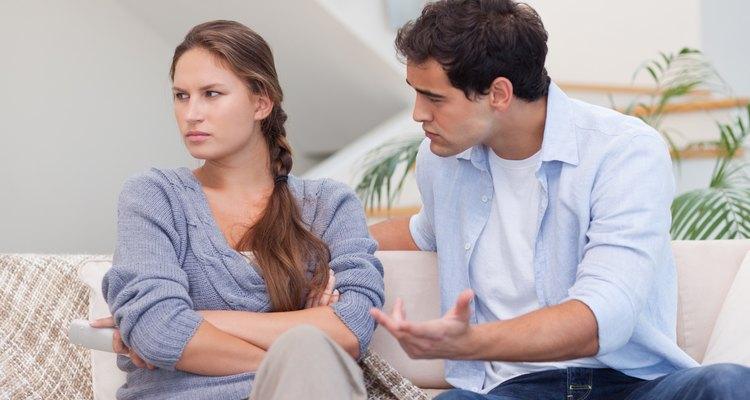 Una pareja tiene una discusión en casa en el sofá.