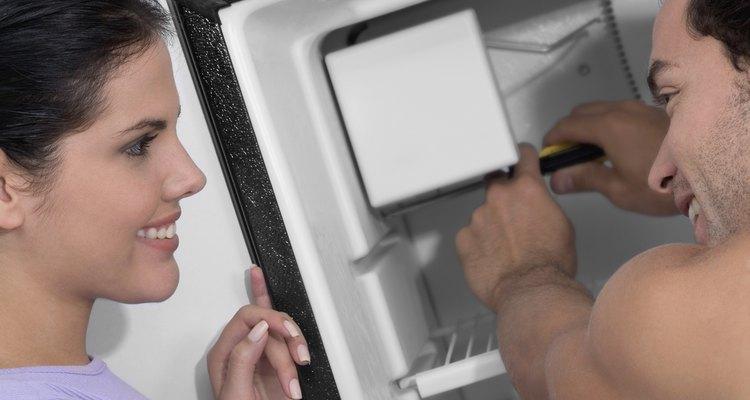 Si necesitas retirar el dispensador de hielo y agua, primero debes quitar la moldura de plástico que oculta los tornillos.