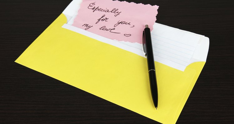 Note in envelope with pen on wooden background