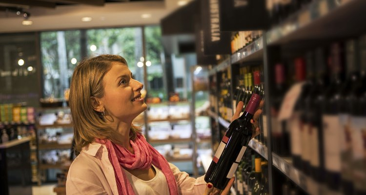 Woman looking for wine on shelves in a a market