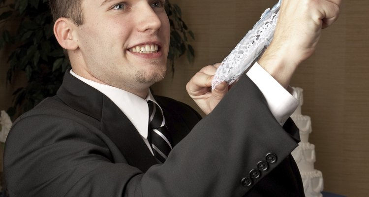 Caucasian groom flipping a garter belt
