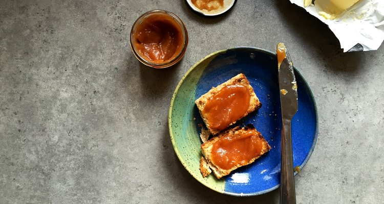 Toasted scone with apple butter on plate in home kitchen