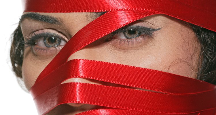 Young woman's face wrapped with a red ribbon