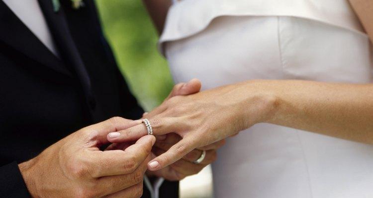 Novio colocando el anillo de bodas en el dedo de su novia.