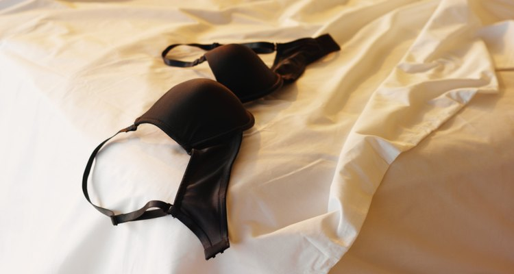 unmade bed with a bra on top of it