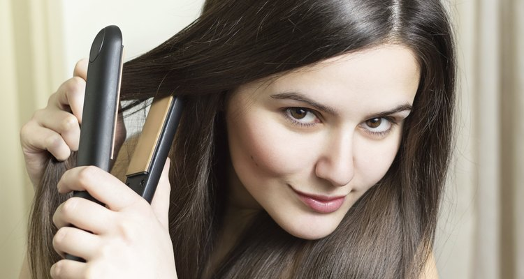 Beautiful young woman straightening hair