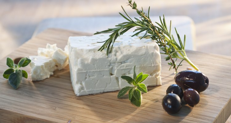 Cheese with herbs on chopping board